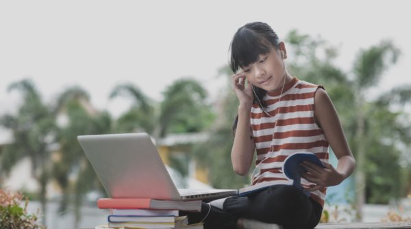 Primary school students in Asia sit and study at a distance from home. online education concept
